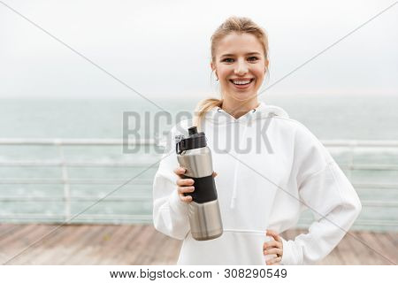 Image of smiling happy woman 20s in white hoodie using earpods and drinking water from bottle while walking near seaside