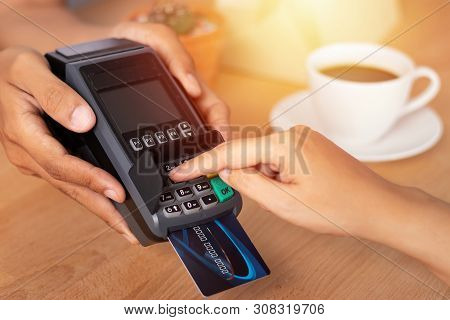 Close Up Of Hand Entering Credit Card Pin Code For Security Password In Credit Card Swipe Machine At