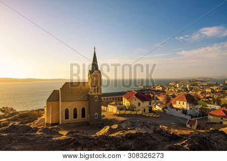 Panoramic View Of Luderitz In Namibia At Sunset With Lutheran Church Called Felsenkirche And Atlanti