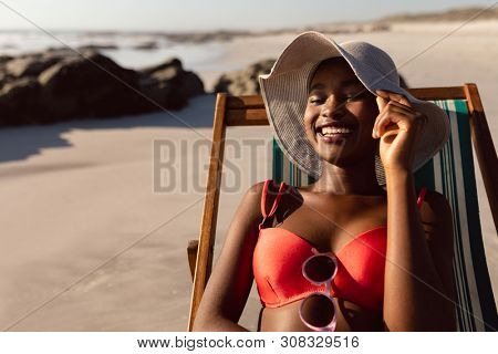 Front view of happy African-american woman relaxing in a beach chair on the beach