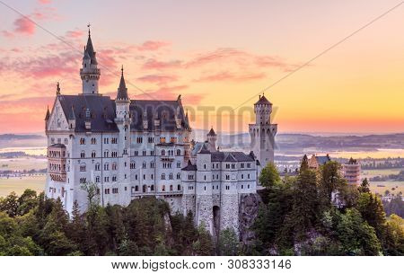 Bavaria, Germany. Fairytale Neuschwanstein Castle in Bavarian Alps mountains. Picturesque view at valley with lake and sunrise sky with clouds. Famous landmark and touristic travel destination.