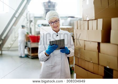 Young Female Dedicated Worker Is Checking Her Tablet While Standing Near The Big Stack Of Cardboard