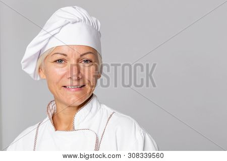 Beautiful smiling middle aged woman in white chef uniform