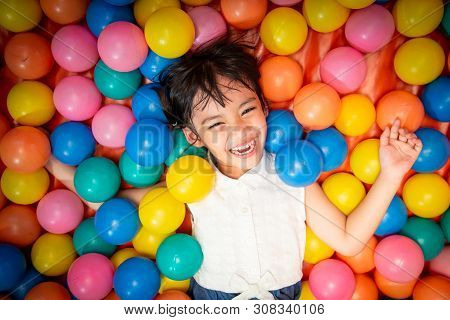 Happy Asian Girl Playing In Colorful Balls Pool