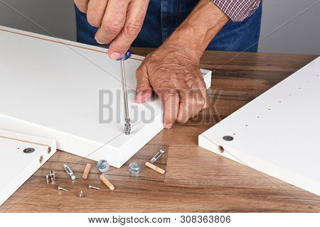 A man assembling a DIY piece of furniture. The person is using a screwdriver to install a piece of hardware.