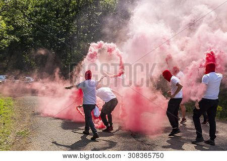 red ultras fans with torches and smokes make an ambush on the street.hooligans with red head masks close the road. poster