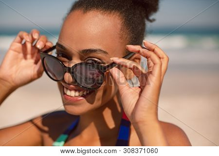 Front view of beautiful happy African american woman looking over sunglasses on beach in the sunshine
