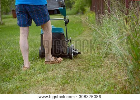The Man Mows A Lawn With The Petrol Lawn-mower In The Warm Summer
