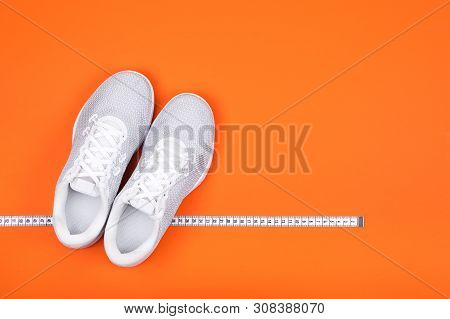 Top View Of White Sport Shoes (sneakers) With Measuring Tape On Russet Orange  Background. Losing We