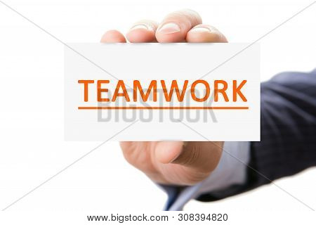 Male Hand On A White Background Shows The Viewer A Card With The Inscription Teamwork.