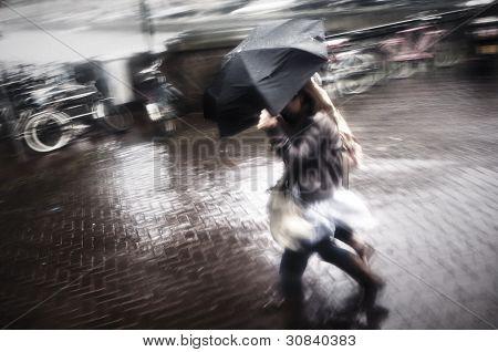 Two women under umbrella in wind