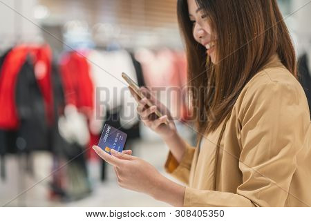 Closeup Asian Woman Using Credit Card With Mobile For Online Shopping In Department Store Over The C