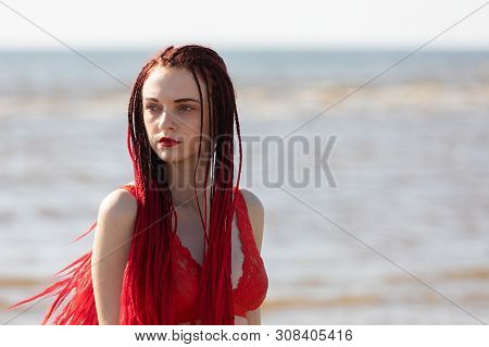 Girl In A Red Bathing Suit On The Beach