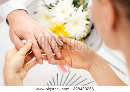 Pedicurist looking at fingernails of man prior to manicure in her studio  poster