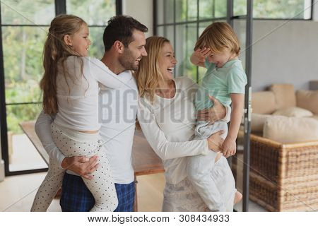 Front view of happy Caucasian parents holding their children at home