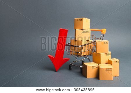 Shopping Cart Supermarket With Boxes And A Red Arrow Down. Falling Consumer Demand, Declining Export