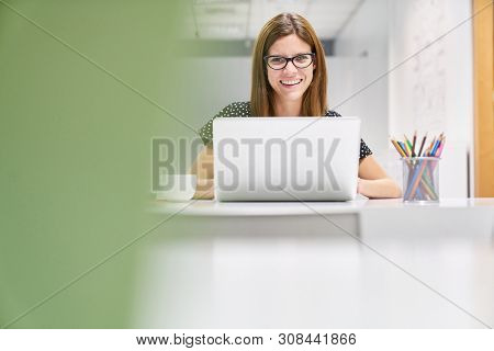 Young business woman as an intern or trainee at laptop computer in the office