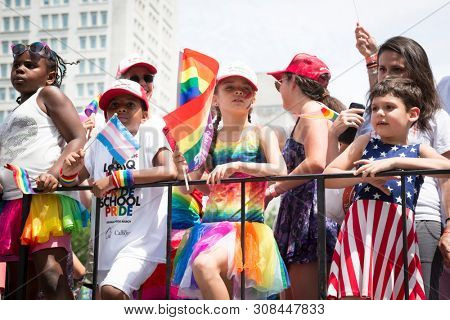 2018 JUNE 24 NEW YORK NYC Pride March: Young children participate with colorful rainbow and American Flag outfits and flags while riding on a parade float along the 5th Ave route.