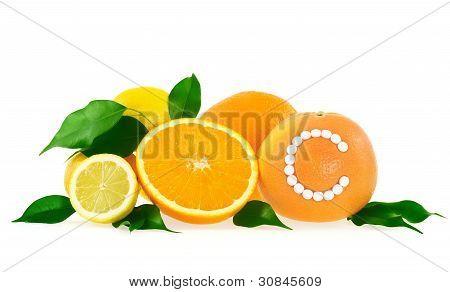Orange lemon grapefruit with vitamin c pills over white background