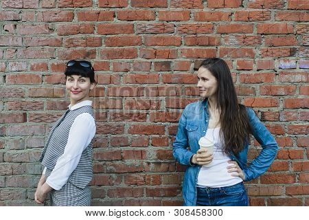 Two Caucasian Women Girlfriends Stand Near Old Grange Red Brick Wall Background In Office And Casual