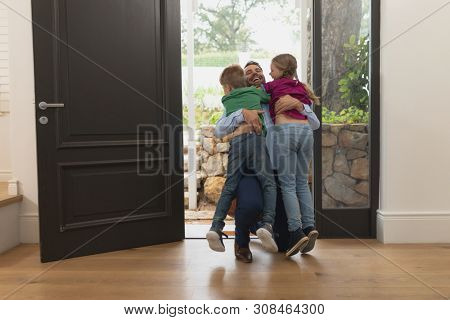 Front view of happy Caucasian father embracing his children as he enters the house