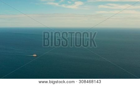 Small Passenger Ferry Cruising In The Open Blue Sea Against Blue Sky With Clouds, Aerial View. Seasc