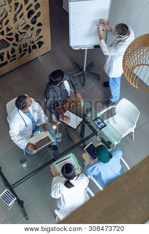 High angle view of Caucasian male doctor explaining graph flip chart in meeting with diverse medical team at hospital . Coffee cup, medical folders, clipboard, digital tablet and laptop are on the