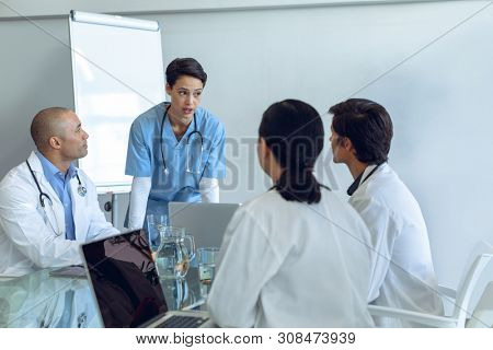 Front view of standing female Caucasian nurse talking to attentive diverse medical team sitting at the table of conference room in hospital