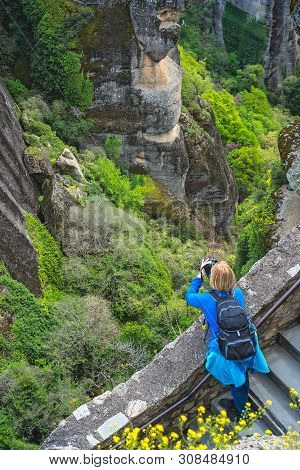 Female Tourist Standing On A Stairs Leading To The Great Meteoron Monastery And Taking Pictures Of T