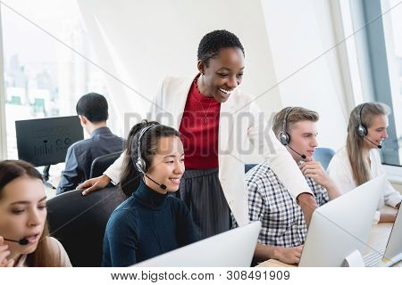 African American female supervisor training work to multiethnic team in call center headquarter office poster