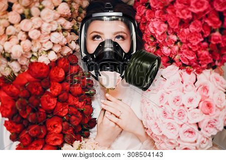 Young Woman Is Smelling Flowers In A Gas Mask. Allergy And Asthmatreatment Concept.