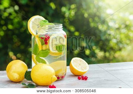 Homemade Lemonade With Fresh Lemons, Mint And Cranberries. A Can Of Lemonade Against A Background Of