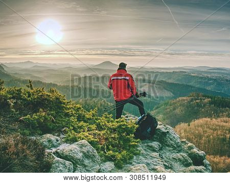 Nature Photographer With Tripod And Camera On Cliff And Thinking. Dreamy Fogy Landscape Orange Misty
