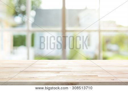Wood Table Top Inside The House With Sunlight Shining Through Window And Blur Green Garden As Backgr