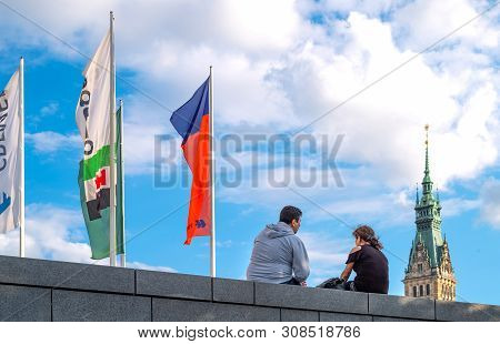 Hamburg, Germany - July 23, 2017: A Young Couple In  Jungfernstieg Stret With Flags And The Town Hal