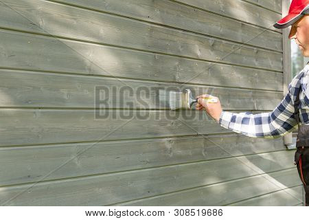 Man Worker Painting Wooden House Exterior Wall With Paintbrush And Wood Protective Color