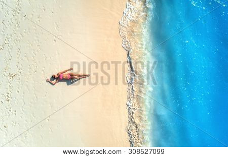Aerial View Of The Beautiful Young Lying Woman On The White Sandy Beach Near Sea With Waves At Sunse