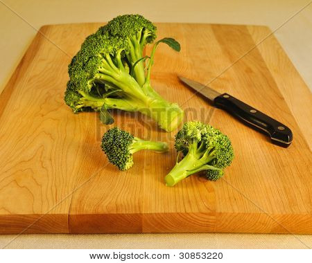 Fresh Green Broccoli on a Wooden Cutting Board with a paring kni