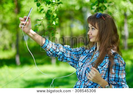 Portrait Of A Beautiful Young Woman Selfie In The Park With A Smartphone