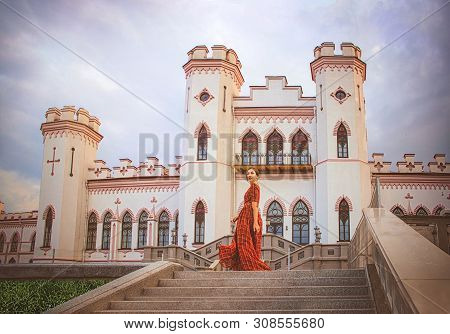 Young Beautiful Princess In A Long Red Dress On The Castle Background In Sunny Day. Art Processing