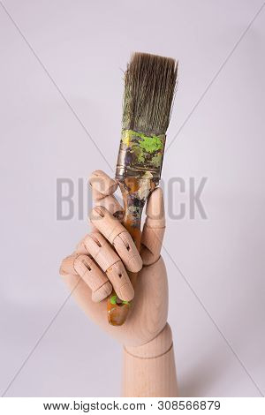 Fake wooden jointed manikin hand holding straight up a art paintbrush studio photo solid background poster