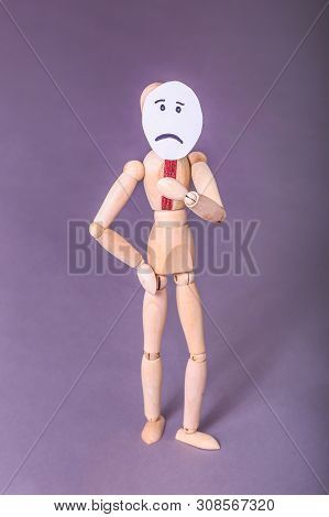 Sad face sign held by wooden jointed manikin doll standing in studio portrait poster