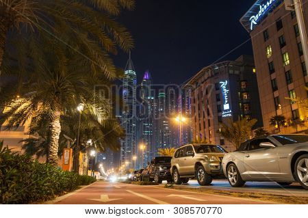 DUBAI, UAE - MARCH 8, 2018: Dubai Night Street with Illuminated Skyscrapers and Palm Trees. Most Known UAE City at Night.