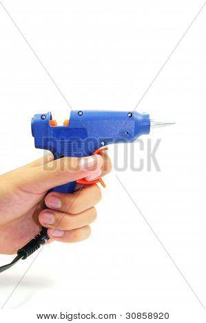 hand holding blue glue gun on white background
