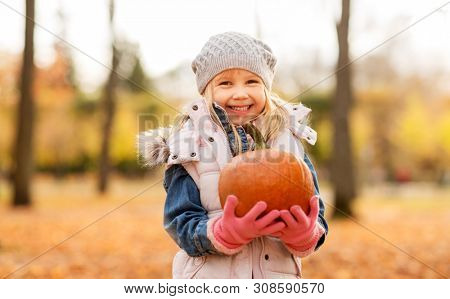 childhood, thanksgiving day and halloween concept - happy little girl with pumpkin at autumn park