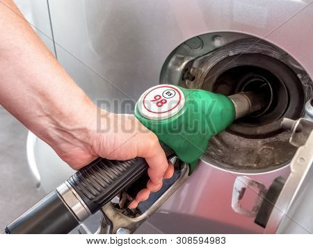 Closeup of female hand topping up car tank with unleaded 98 gasoline
