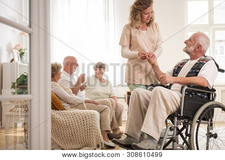 Senior Man On Wheelchair With Helpful Nurse Holding His Hand And Friends Sitting On Couch Drinking T