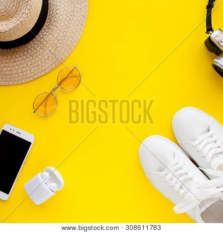 White Sneakers, Hat, Sunglasses, Wireless Headphones, Smartphone And Photo Camera Are Lying On A Yel