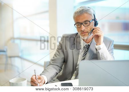 Mature businessman on conference call with headpiece