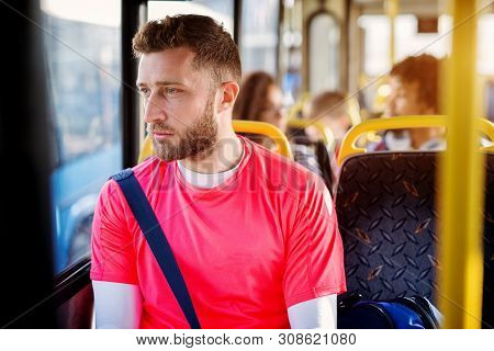 Young Handsome Man Is Sitting In The Bus And Looking At Distance Trough The Window.
